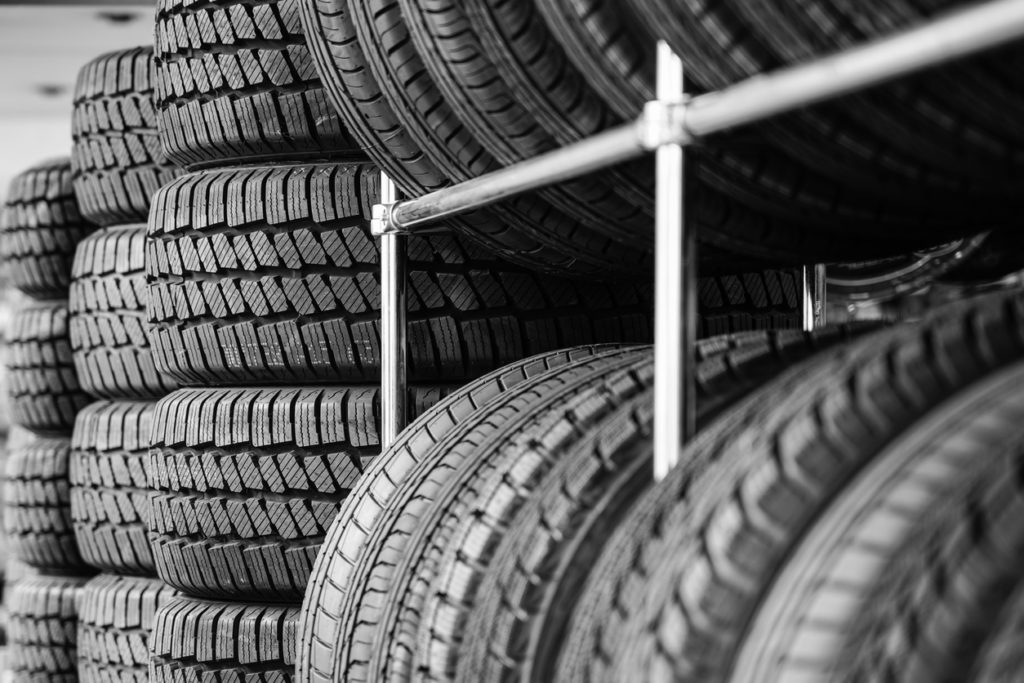 Rack with variety of new car tires in automobile store